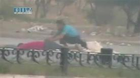 <p>EDITOR'S NOTE: REUTERS CANNOT INDEPENDENTLY VERIFY THE CONTENT OF THE VIDEO FROM WHICH THIS STILL IMAGE WAS TAKEN A protester crouches near the body of a man lying on the ground in Hama in this still image taken from video posted on a social media website on August 4, 2011. REUTERS/Social media website via Reuters TV</p>
