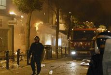 Пожарные пытаются потушить огонь в магазине в Вулвиче на юго-востоке Лондона, 9 августа 2011 года. Массовые беспорядки продолжают бушевать в Лондоне - в городе третью ночь подряд горят машины и здания, молодежь бьет витрины магазинов и забрасывает полицию камнями и бутылками. REUTERS/Jon Boyle