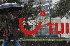 Женщина проходит мимо логотипа TUI AG возле штаб-квартиры компании в Ганновере, 25 марта 2009 года. Высокий спрос на рынках Великобритании и скандинавских стран позволил TUI Travel, крупнейшему туроператору Европы, улучшить показатели во втором квартале 2011 года. REUTERS/Christian Charisius