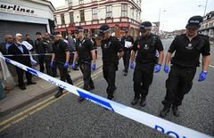 Police officers examine the scene where three men were killed by a car in the Winson Green area of Birmingham, central England August 10, 2011. REUTERS/Andrew Winning