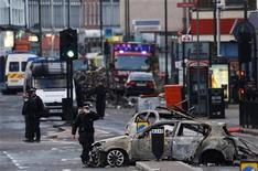 Policiais vasculham rua de Tottenham, no norte de Londres, após distúrbios na região. 07/08/2011 REUTERS/Luke MacGregor