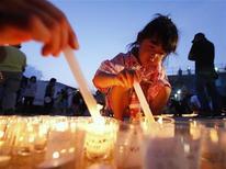 """Menina acende velas em evento para lembrar as vítimas do terremoto e tsunami de 11 de março em Kesennuma, no Japão. Crianças na cidade devastada acenderam 10 mil velas e soaram os tambores taiko nesta sexta-feira na véspera do """"obon"""", uma cerimônia budista que homenageia os mortos, enquanto moradores lutam para reconstruir suas vidas cinco meses depois do desastre. 12/08/2011 REUTERS/Kim Kyung-Hoon"""