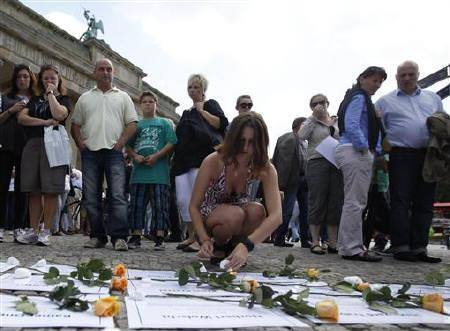 A woman places a rose on a paper with the name of a person killed while trying to escape from East Berlin by crossing the Berlin Wall during a ceremony at the Brandenburg Gate in Berlin, August 13, 2011. TREUTERS/Pawel Kopczynski/Files