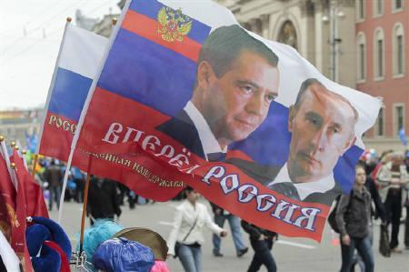 A Russian flag with portraits of President Dmitry Medvedev (L) and Prime Minister Vladimir Putin is seen on sale near a May Day rally organised by Russian Trade Unions on International Workers' Day, or Labour Day, through central Moscow May 1, 2011. The flag reads, ''Forward Russia!''. REUTERS/Alexander Natruskin