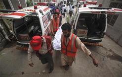 Спасатели везут труп человека к моргу в Карачи 18 августа 2011 года. Новая волна беспорядков охватила финансовый центр Пакистана город Карачи в среду и четверг, в результате чего по меньшей мере 39 человек были убиты, сообщили власти.  REUTERS/Akhtar Soomro