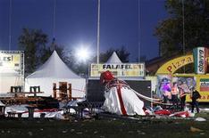 Policiais observam barraca destruída por uma forte tempestade no festival de música Pukkelpop, no norte da Bélgica. Subiu para cinco o número de mortos por causa da tempestade que derrubou telões e tendas no festival, disseram autoridades nesta sexta-feira. 18/08/2011  REUTERS/Sebastien Pirlet