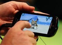 <p>Un visiteur du salon du jeu vidéo Gamescom joue sur son smartphone. Cette pratique de plus en plus répandue avec des jeux gratuits offre une source de développement et de revenus nouvelle pour les éditeurs. /Photo prise le 17 août 2011/REUTERS/Ina Fassbender</p>