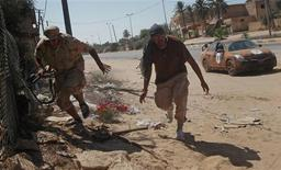 Libyan rebel fighters run for cover from incoming fire as they advance through the town of Maia, 25 kms (15 miles) from Tripoli, August 21, 2011.   REUTERS/Bob Strong