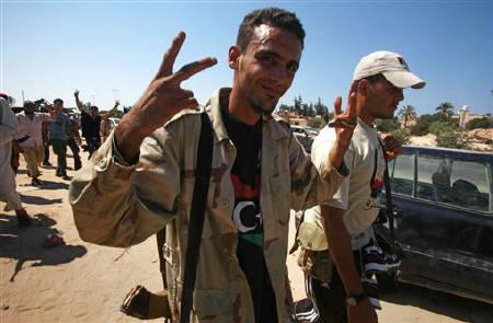 A Libyan rebel fighter celebrates as rebels advance through the town of Maia, 25 kms (15 miles) west of Tripoli, August 21, 2011. REUTERS/Bob Strong
