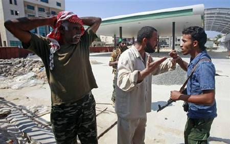 A man argues with a Libyan rebel fighter (R) after rebels tried to detain one of his workmen (L) near a checkpoint in Tripoli's Qarqarsh district August 22, 2011. REUTERS/Bob Strong