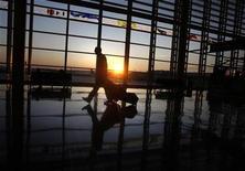 <p>A traveller walks to his flight at Ronald Reagan National Airport as the sun rises in Washington, September 24, 2008. REUTERS/Jason Reed</p>