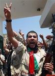 """<p>Un grupo de rebeldes celebra tras tomar el control del centro de oficiales femeninos del Ejército libio en el distrito de Qarqarsh en Trípoli, ago 22 2011. Tanques y francotiradores del Gobierno libio defendían el lunes los últimos reductos de resistencia en Trípoli, luego de que los rebeldes llegaran al centro de la capital alentados por una multitud que anunciaba el fin de 42 años de Muammar Gaddafi en el poder. El líder de 69 años, que instó a los civiles a tomar las armas contra las """"ratas"""" rebeldes, dijo en una grabación de audio que estaba en la ciudad y que permanecería allí """"hasta el final"""". REUTERS/Bob Strong</p>"""