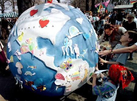Polish youngsters attach pictures of animals they have drawn to a large globe April 21, 1996 as part of Earth Day celebrations in a Warsaw park. REUTERS/Pawel Kopczynski/Files