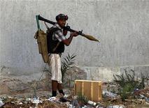 Повстанец с РПГ в столице Ливии Триполи 25 августа 2011 года. Ливийские повстанцы бросили на поиски многолетнего лидера страны Муаммара Каддафи специальные отряды, а их руководство переедет из Бенгази в  столицу Триполи. REUTERS/Goran Tomasevic
