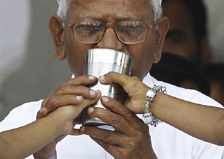 Anna Hazare drinks coconut water and honey to end his fast at Ramlila grounds in New Delhi August 28, 2011. REUTERS/Adnan Abidi