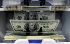Кассовый аппарат считает долларовые банкноты в банке в Берне, 15 августа 2011 года. Доллар снизился к корзине валют в понедельник, так как инвесторы услышали в пятничном выступлении главы ФРС Бена Бернанке намеки на дальнейшее стимулированию застопорившейся американской экономики, что повысило глобальный аппетит к риску. REUTERS/Pascal Lauener