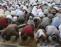 <p>Indonesian Muslims attend prayers marking the end of the fasting month of Ramadan on a street in Jakarta August 30, 2011. REUTERS/Supri</p>