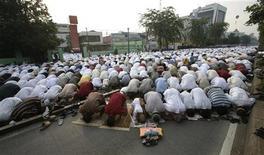 Индонезийские мусульмане во время молитвы в честь окончания месяца Рамадан на улицах Джакарты 30 августа 2011 года. Правительство Индонезии объявило, что луна находится не в подходящем положении для окончания месяца Рамадан, завершение которого ожидалось во вторник.   REUTERS/Supri