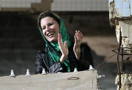 Aisha Gaddafi, daughter of Libya's leader Muammar Gaddafi, claps during a pro-government rally at the heavily fortified Bab al-Aziziya compound in Tripoli, April 14, 2011. REUTERS/Louafi Larbi