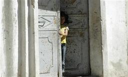 Юная жительница Сирии стоит на пороге дома в Хаме, 11 августа 2011 года. Сирийские военные вторглись в дома мирных жителей в поисках активистов в двух главных районах Хамы в среду, сообщают местные жители. REUTERS/Mehmet Emin Caliskan