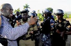 Uganda's Forum for Democratic Change (FDC) leader Kizza Besigye (L) talks to anti-riot policemen before his arrest at Kasangati suburb of the capital Kampala, April 11, 2011.  REUTERS/Edward Echwalu