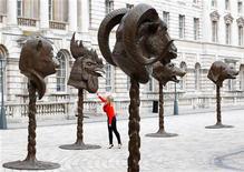 """Mulher observa a instalação itinerante de Ai Weiwei """"Círculos de Animais/Cabeças do Zodíaco"""" em Londres. A instalação foi inaugurada há duas semanas no Museu de Arte do Condado de Los Angeles, apresentando ao público o trabalho de um homem que, até recentemente, só era conhecido por causa das notícias sobre sua recente detenção na China. Foto de Arquivo. 11/05/2011 REUTERS/Andrew Winning"""
