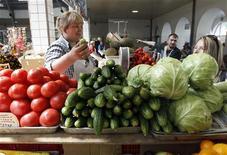 Женщина продает овощи на рынке в Санкт-Петербурге, 2 июня 2011 года. Индекс потребительских цен в РФ снизился в последний месяц лета впервые с августа 2005 года, оказавшись лучше прогнозов властей и аналитиков, сообщил Росстат в понедельник. REUTERS/Alexander Demianchuk