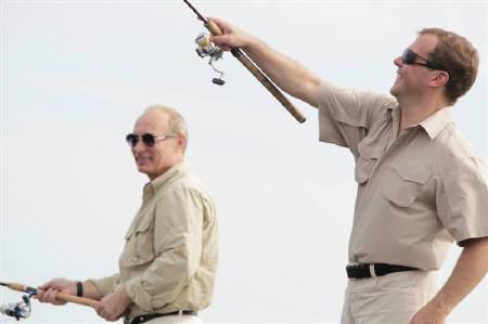 Russian President Dmitry Medvedev (R) and Prime Minister Vladimir Putin enjoy some fishing on the river Volga in Russia's Astrakhan region August 16, 2011. REUTERS/Mikhail Klimentyev/RIA Novosti/Kremlin/Files