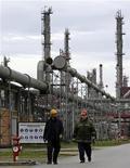 Рабочие идут по территории нефтеперерабатывающего завода в 20 километрах от Белграда, 5 декабря 2008 года. Итальянская Eni получит долю 20-процентную долю в проекте газопровода Южный поток, немецкая BASF и французская EDF - по 15 процентов, сказал глава российского концерна Газпром Алексей Миллер. REUTERS/Ivan Milutinovic