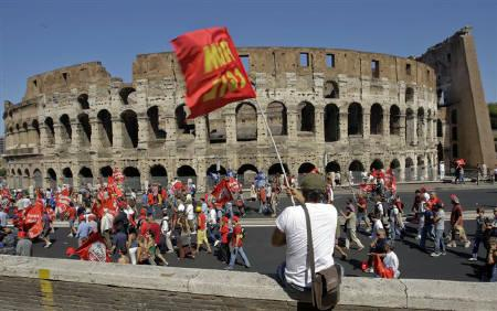 A demonstrator waves a flag in front of the Colosseum during a demonstration in Rome, September 6, 2011. Protesters in Italy scuffled with police, burned flags and threw eggs and smoke bombs at banks on Tuesday in what they said could be a taste of escalating public disorder as public spending cuts bring pain to families. REUTERS/Remo Casilli