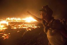 """<p>Kristine Green throws a letter into the fire as the Temple of Transition burns during the Burning Man 2011 """"Rites of Passage"""" arts and music festival�in the Black Rock desert of Nevada, September 4, 2011. More than 50,000 people from all over the world have gathered at the sold out festival which is celebrating its 25th year. REUTERS/Jim Urquhart</p>"""