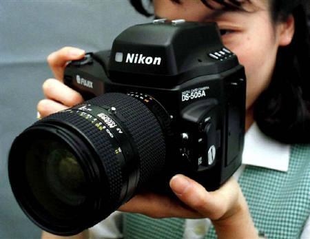 Fuji Photo Film promotion representative Miyoko Ohura demonstrates the new upgraded DS505A digital camera, developed by Fuji Photo Film and Nikon Corp August 21. REUTERS/Susumu Toshiyuki