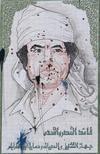 Поврежденное изображение Муаммара Каддафи на улице в Триполи 10 сентября 2011 года. Сирийский телеканал объявил в понедельник, что свергнутый повстанцами и скрывающийся от международного суда ливийский лидер Муаммар Каддафи остается на родине и ведет борьбу. REUTERS/Suhaib Salem