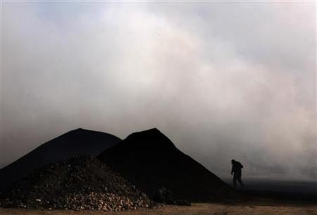 A worker at the Jinyuan Company's smelting workshop for rare earth metals, walks through thick smoke billowing from factories next door near the town of Damao, in China's Inner Mongolia Autonomous Region October 31, 2010. REUTERS/David Gray