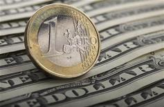 Монета валюты евро на банкнотах доллара США в Варшаве 26 января 2011 года. Евро снизился в пятницу на фоне фиксации прибыли инвесторами после ралли, вызванного обещанием центральных банков мира дать ликвидность банковской системе Европы, и может увеличить потери, если министры финансов еврозоны не смогут согласовать дальнейшие меры борьбы с долговым кризисом на встрече в Польше. REUTERS/Kacper Pempel