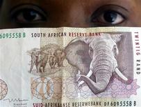 A bank teller looks at South African rand note, October 1, 2003.