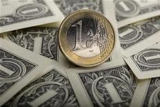 Монета в 1 евро на долларовых купюрах в Варшаве, 18 января 2011 года. Евро начал понедельник падением, так как политические неудачи на минувших выходных спровоцировали бегство от риска. REUTERS/Kacper Pempel