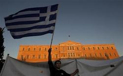 Водитель такси размахивает греческим флагом перед зданием парламента в Афинах, 13 сентября 2011 года. Международные кредиторы в понедельник потребовали от Греции сократить долю госсектора в экономике, чтобы не опустошить казну уже через несколько недель. REUTERS/John Kolesidis
