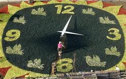 Садовники делают клумбу ввиде часов в Киеве, 20 августа 2009 года. Украина вслед за соседями - Россией и Белоруссией - отказалась от перехода нынешней осенью на зимнее время. REUTERS/Konstantin Chernichkin