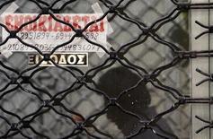 Мужчина отражается в витрине закрытого магазина в Афинах, 19 сентября 2011 года. Греция в среду пообещала еще сильнее урезать пенсии, продлить налог на недвижимость и уволить в резерв десятки тысяч госслужащих ради очередной порции кредитов ЕС и МВФ. REUTERS/John Kolesidis