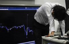 """Трейдер стоит около информационного табло на бирже в Токио, 26 июля 2011 года. Фондовые рынки Азии закрылись в пятницу снижением из-за страха перед новой рецессией развитых экономик, не вдохновленные обещанием денежных властей """"Большой двадцатки"""" сохранять финансовую стабильность. REUTERS/Yuriko Nakao"""