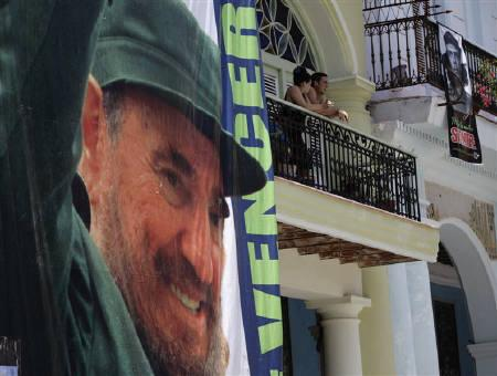 People look from a balcony beside a poster of former Cuban leader Fidel Castro in Havana August 13, 2011. Castro accused U.S. President Obama of speaking ''gibberish'' in his recent address to the United Nations and called NATO's actions in Libya a ''monstrous crime'' on Monday in his first opinion column since early July. REUTERS/Desmond Boylan/Files