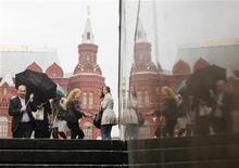 Люди идут по улице рядом с Историческим музеем в Москве, 18 мая 2011 года. Последняя неделя сентября в Москве будет пасмурной и холодной, ожидают синоптики. REUTERS/Denis Sinyakov