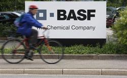 Мужчина проезжает на велосипеде мимо логотипа BASF близ Базеля, 7 июля 2009 года. Российский агрохимический холдинг Еврохим намерен купить у немецкой BASF активы по производству минеральных удобрений в Бельгии, а также половину предприятия PEC-Rhin во Франции REUTERS/Christian Hartmann