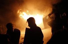 Болгарские полицейские у горящего здания во во время волнений в деревне Катуница в 160 километрах к востоку от Софии 24 сентбяря 2011 года. Сотни людей вышли на улицы Болгарии, закидывая полицейских бутылками и камнями после инцидента между жителями одной из местных деревень и лидером цыганского клана, что стало самой серьезной вспышкой насилия в самой бедной стране Евросоюза за долгие годы. REUTERS/Stoyan Nenov