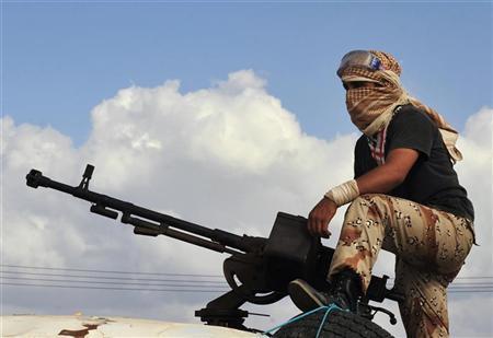 An anti-Gaddafi fighter takes position behind his anti-aircraft gun, 2 km (1.2 miles) east of Sirte September 27, 2011. REUTERS/Esam Al-Fetori (LIBYA - Tags: CIVIL UNREST CONFLICT)