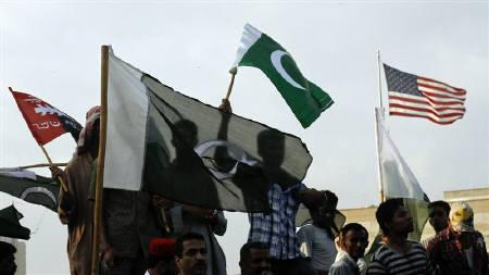 An U.S. flag (R) flutters above the U.S. consulate as supporters of the Pakistan People's Party (PPP) wave their national flags during an anti-American rally in Karachi September 27, 2011. REUTERS/Athar Hussain