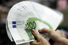 Сотрудница банка Bank of Taiwan держит веер из купюр по 100 евро, 10 мая 2010 года. Евро уверенно растет к доллару и иене в четверг благодаря ожиданиям инвесторов, что парламент Германии одобрит расширение Европейского фонда финансовой стабильности (EFSF), хотя скептицизм относительно долгосрочной стабильности в еврозоне может ограничить дальнейший рост. REUTERS/Pichi Chuang