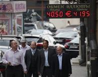 Мужчины проходят мимо обменного пункта в Москве, 9 августа 2011 года. Курс рубля снизился в на торгах в четверг из-за окончания налогового периода, дешевеющей нефти и сохраняющихся опасений о долговом кризисе в еврозоне. REUTERS/Grigory Dukor
