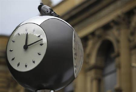 A pigeon sits on a clock in front of the Frankfurt stock exchange, August 25, 2011. REUTERS/Alex Domanski